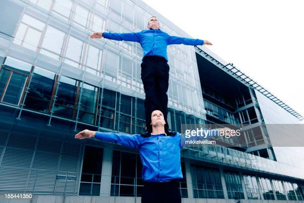 One businessman stands on the shoulder of another