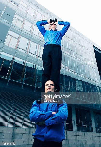Ein Geschäftsmann mit Fernglas ist auf der Schulter des coworker