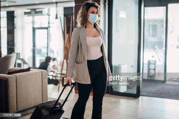 one businesswoman with protective face mask arriving at a hotel lobby - south_agency stock pictures, royalty-free photos & images