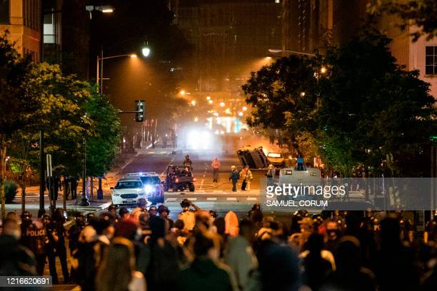 One car is flipped over while another one burns as protestors and police face off near the White House protesting the death of George Floyd at the...