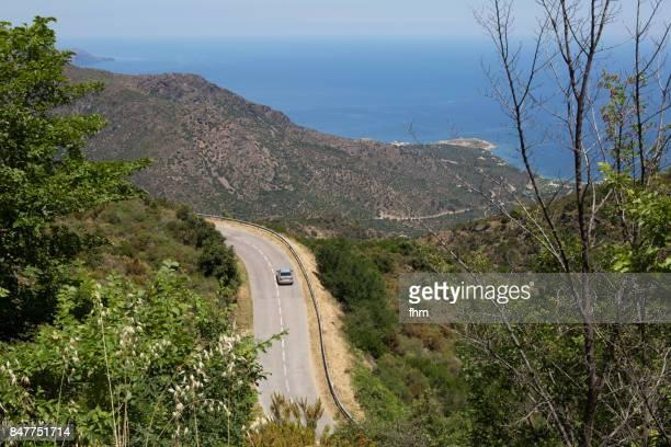 One car on the curvy road in the mountains of catalonia with mediterranean sea in the background (near Porta de la Selva, Catalonia/ Spain)