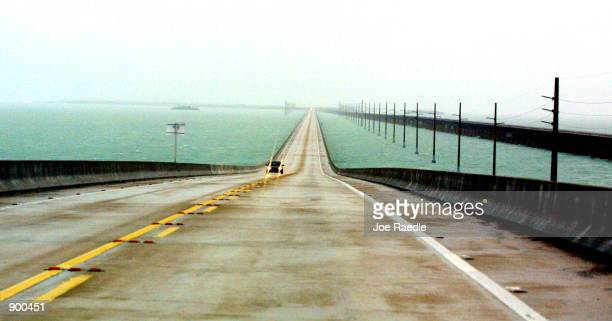 One car travels north on the Seven Mile Bridge November 4, 2001 as Hurricane Michelle approaches the Florida Keys. The hurricane is sustaining 140...