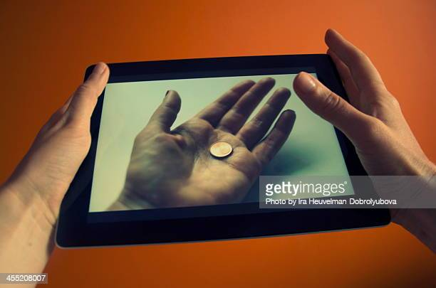 one cent on handpalm on digital tablet screen