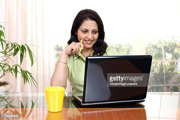 One Cheerful Indian Businesswoman Using Laptop