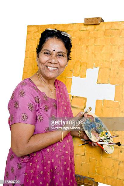 one cheerful indian senior woman artist working on her painting - jesus is alive stock pictures, royalty-free photos & images