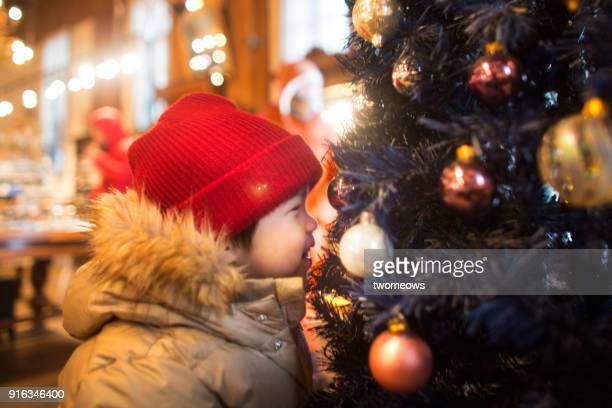 One child closely looking at Christmas tree decoration reflection.