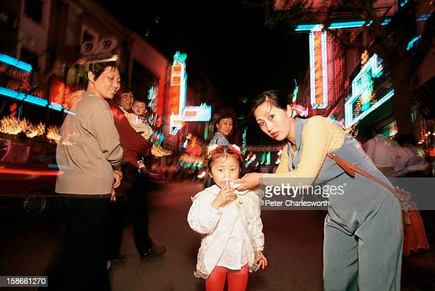One child families Parents with their child walk in the evening on the neonlit Nanjing Road China has a strict one child family policy
