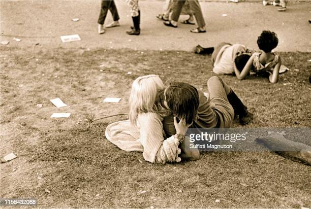 One couple kissing on the grass, another comfortable intertwined at the 1st Elysian Park Love-In on March 26, 1967 in Los Angeles, California.