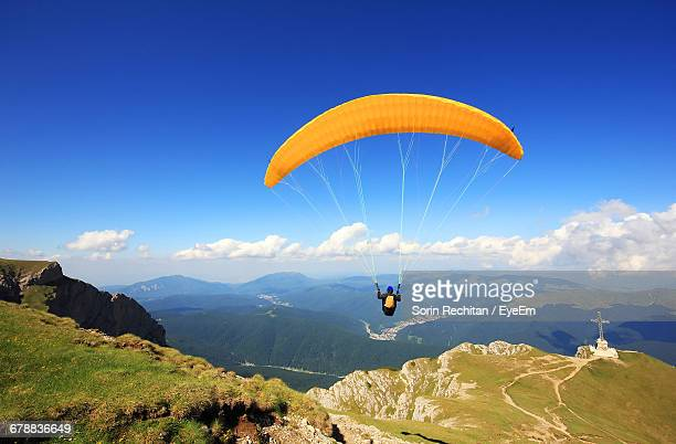 One Courageous Person Paragliding Over Mountains