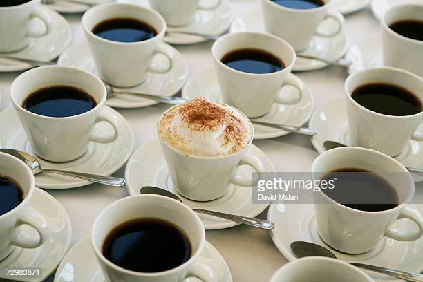 One cup of cappuccino amongst cups of black coffee, elevated view