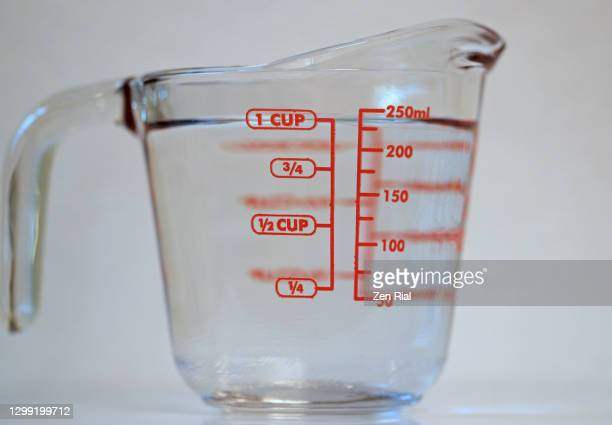 one cup of clear water in a measuring glass cup with handle on white background - measuring cup stock pictures, royalty-free photos & images