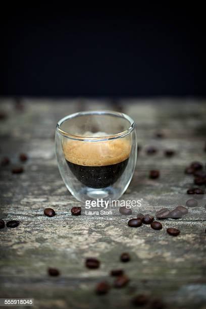 One dark espresso coffee shot and beans