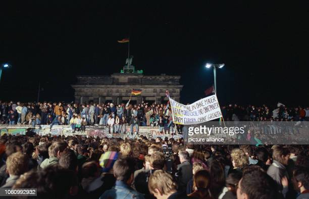 One day after the opening of the border, thousands of people celebrate on, in front of and behind Berlin Wall at Brandenburg Gate in Berlin on 10...