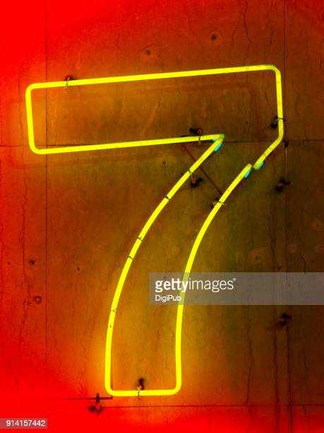 One digit number seven neon sign on concrete wall