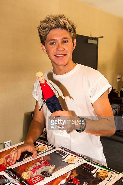 One Direction band member Niall Horan poses with his doll at the One Direction Private Concert Fan Chat Hosted by Hasbro at W Westwood on August 6...