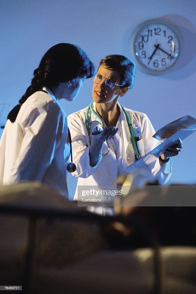 One doctor instructing another : Stockfoto