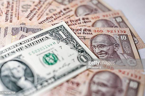 A US one dollar banknote and Indian ten rupee banknotes are arranged for a photograph in Mumbai India on Saturday Aug 10 2013 India plans to sell 220...