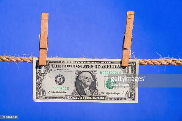 us one dollar bill hanging on a clothesline - money laundering stock photos and pictures