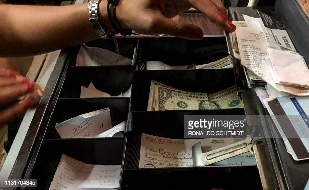 A one dollar bill is seen at the cash drawer of a restaurant in Caracas on March 18 2019 Whether paying for a manicure an evening gown or a liter of...