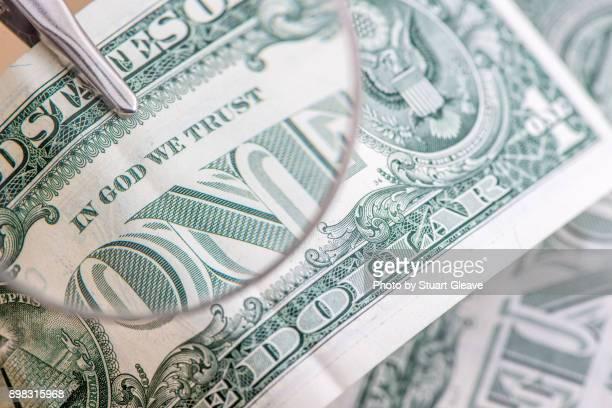 One dollar bill under magnifying glass