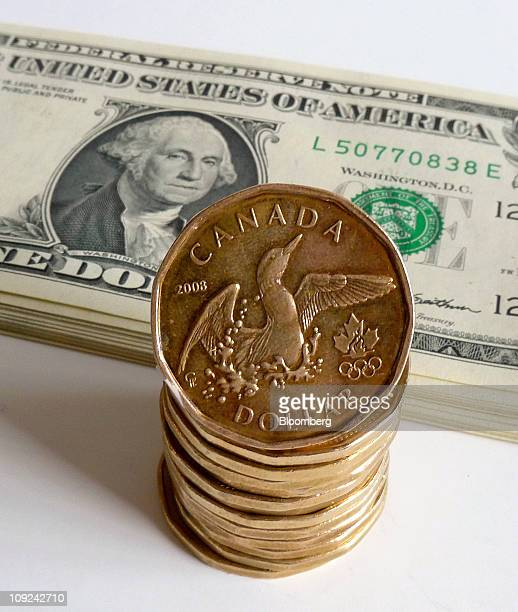 US one dollar bills and Canadian one dollar coins called loonies as the currency is known for its image of the aquatic bird are arranged for a photo...