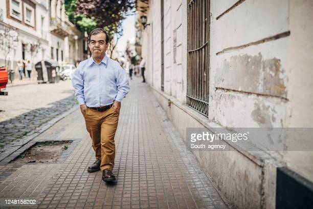 one dwarf man walking down the street - dwarf man stock pictures, royalty-free photos & images
