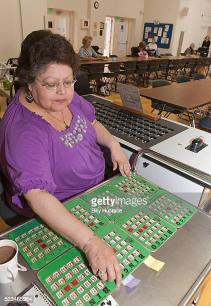 One elderly woman leisurely playing a game of bingo