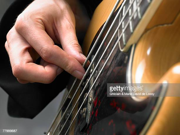 one electric guitar player close up on hand. - ベースギター ストックフォトと画像