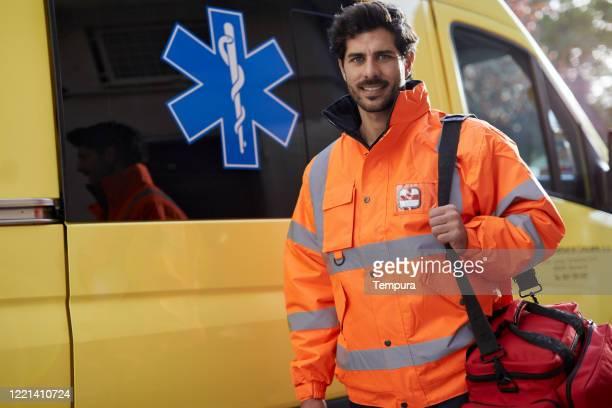 one emergency worker standing next to the ambulance and looking at camera. - rescue worker stock pictures, royalty-free photos & images