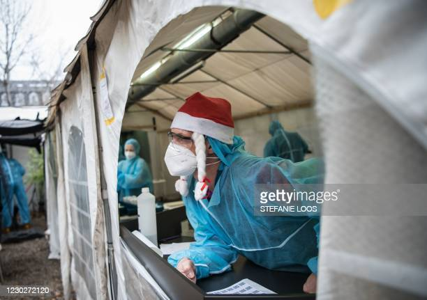 One employee wearing PPE and a Christmas hat calls the next patient to take a swab to test for the Covid-19 coronavirus, outside the Berlin...