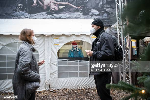 One employee wearing PPE and a Christmas hat is seen as patients queue for a swab to test for the Covid-19 coronavirus outside the Berlin KitKatClub...