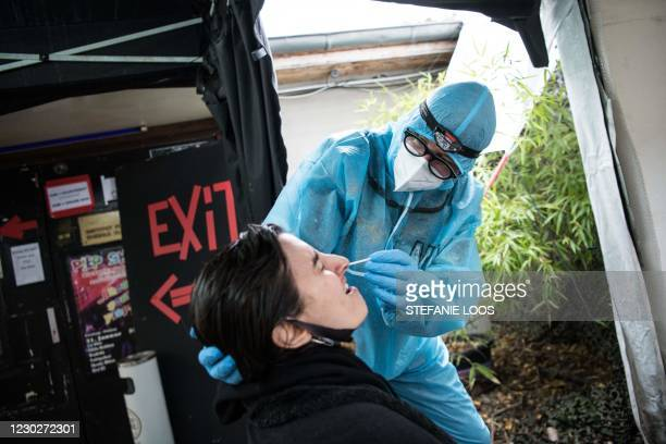 One employee wearing PPE takes a swab from a woman to test for the Covid-19 coronavirus, outside the Berlin KitKatClub night club, turned into a...