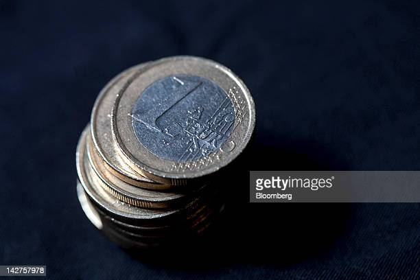 A one euro coin sits on top of a stack of mixed denomination euro coins in this arranged photograph in London UK on Thursday April 12 2012 The euro...