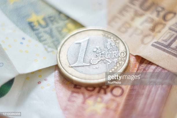 One Euro Coin, stacked money on euro coins and banknotes in the background. Euro coins are portraying the value and a map of Europe, but each country...