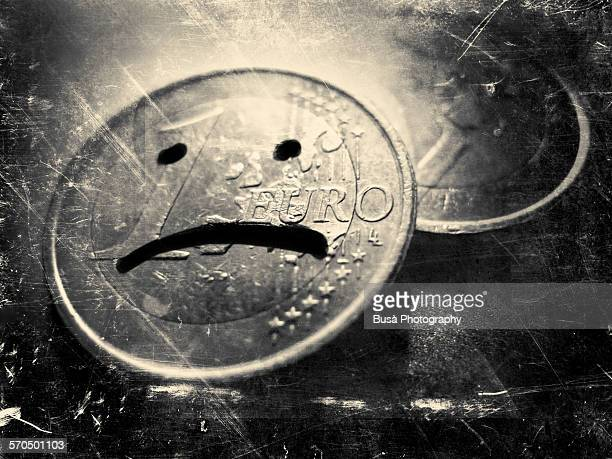 A one euro coin with a sad face on it