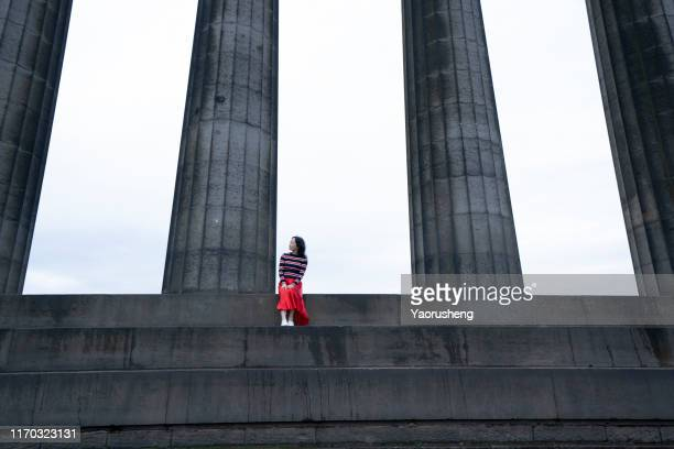 one female adault vivit the national monument of scotland in the morning - カールトンヒル ストックフォトと画像