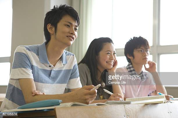 One female and two male students sitting in classroom