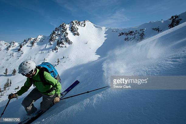 One female telemark skier making a hard turn.