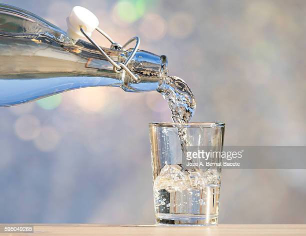 One fills water glass of a bottle of crystal