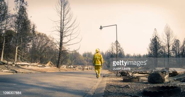 one firefighter wearing bright yellow protective gear and helmet walks alone along a street where every home burned to the ground, paradise fire 2018 - california wildfire stock pictures, royalty-free photos & images