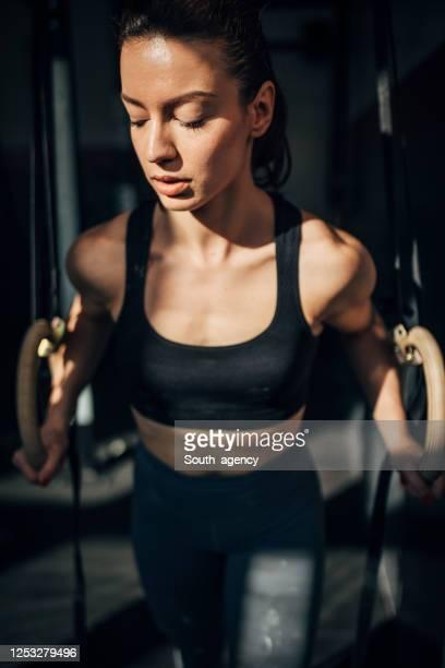 eine fitte frau, die auf gymnastikringen im fitnessstudio trainiert - frauen ringen stock-fotos und bilder