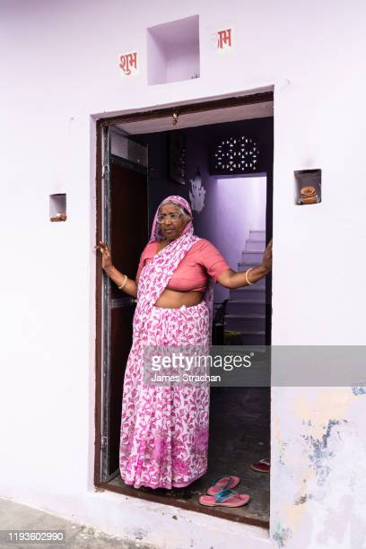 one full length portrait of senior gujar woman at her front door in pink sari (clothing) offset against the mauve colour of the walls and interior of her house, pushkar, rajasthan, india (model release) - james strachan stock pictures, royalty-free photos & images
