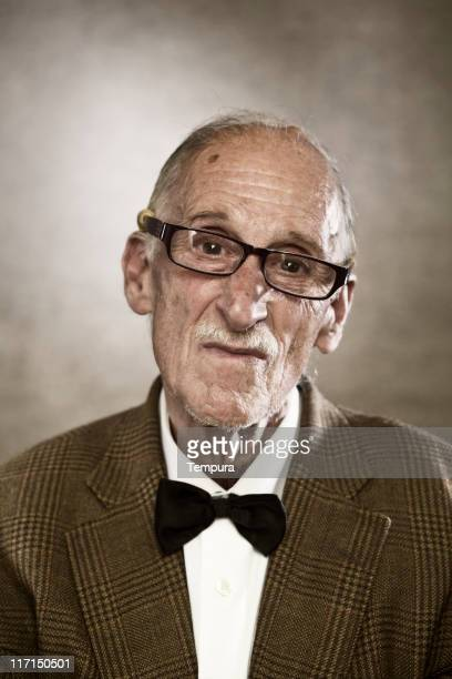 One gentle old man with glasses looking at you