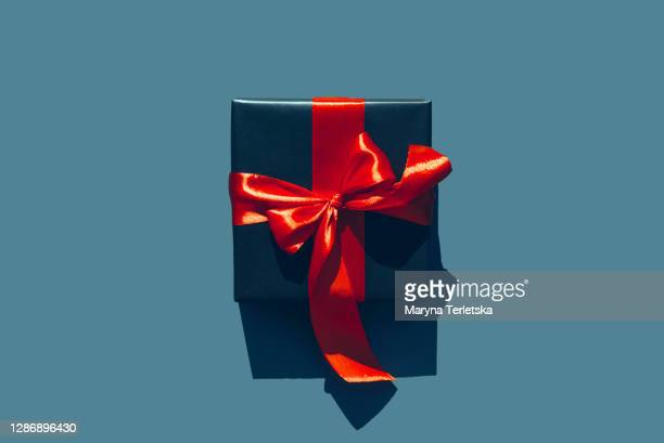 one gift with a large satin red bow. - satin stock pictures, royalty-free photos & images