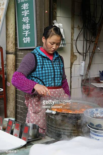 CONTENT] One girl is cooking the bread In Pekin there are many shops and markets food is sold on the street now known as street food