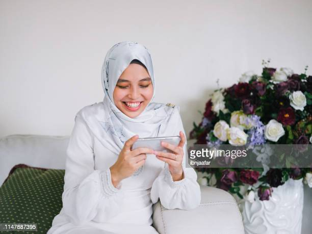 one girl playing game with phone - eid ul fitr photos stock pictures, royalty-free photos & images
