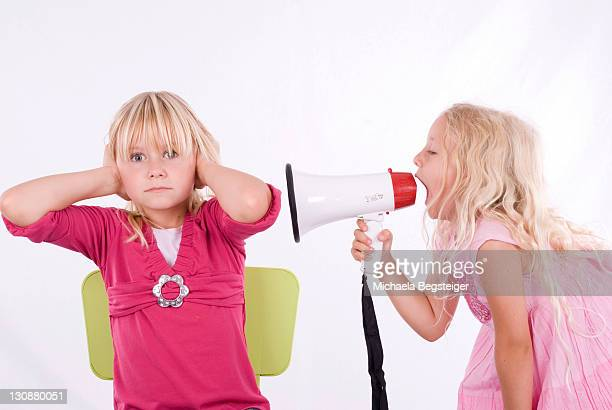 One girl screaming at another through a megaphone