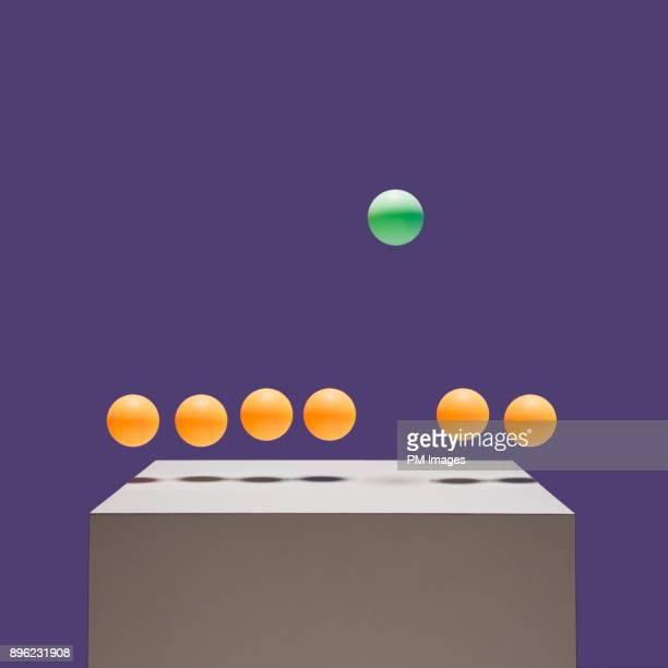 One green ball bouncing higher than 6 orange balls