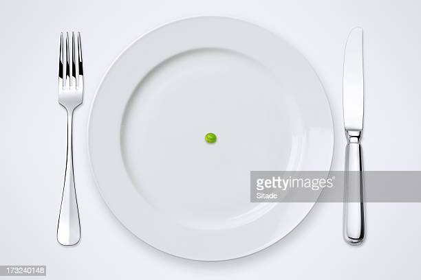 one green pea on plate. table setting with clipping path. - silverware stock pictures, royalty-free photos & images