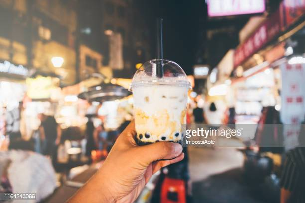 one hand holding bubble milk tea glass at night street market in taiwan with blurred chinese letters in the background - taipei fotografías e imágenes de stock